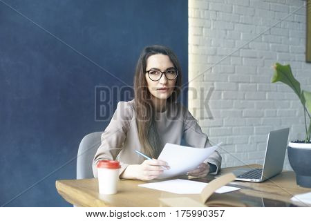 Beautiful businesswoman with long hair working with documentation sheet laptop while sitting in modern loft office. Dark blue wall background day light