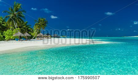 Palm trees and beach umbrelllas over lagoon and white sandy beach, Maldives island