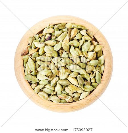 Green cardamon seeds in wooden dish isolated on white background Saved clipping path.