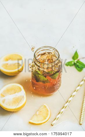 Summer cold Iced tea with fresh bergamot, mint and lemon in glass jar with splashes on light table background, copy space. Food in motion concept