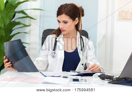 Smiling confident female doctor sitting at office desk and examining a patient's x-ray