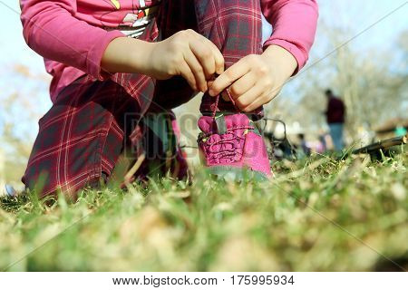 small girl tying shoelaces outdoor in park