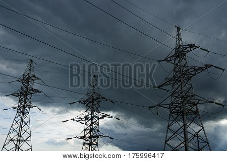 High voltage electricity pylons against thundercloud. Electric pole power lines and wires.