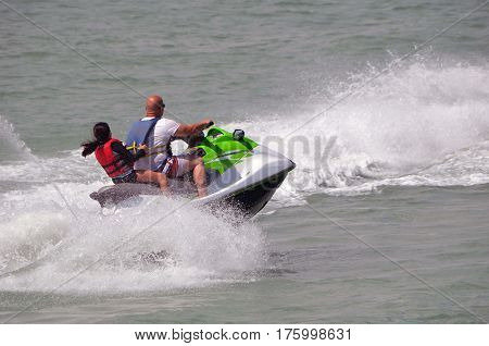 Father and daughter enjoying a high speed jet  ski cruise on the florida intra-coastal waterway.