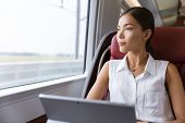 Asian woman traveling using laptop in train. Businesswoman pensive looking out the window while working on computer on travel commute to work. poster