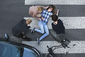 Passersby helping an unconscious casualty of a car accident lying next to the bike poster