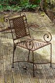 Rusty abandoned chair on neglected wooden decking in an overgrown poorly maintained garden poster