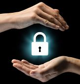 Isolated image of two hands on black background. Lock icon in the center as a symbol of confidentiality data protection and security. Concept of confidentiality data protection and security. poster