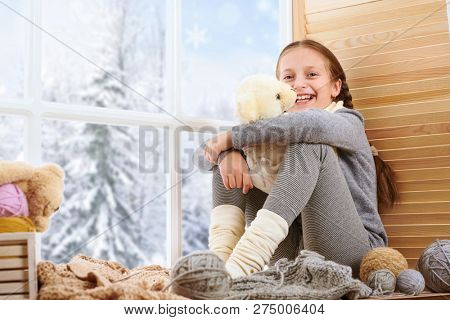 Child girl is sitting on a window sill and playing with bear toy. Beautiful view outside the window - sunny day in winter and snow.