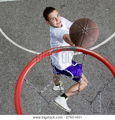 Young basketball player on the street going  to the hoop. Great angle from above.