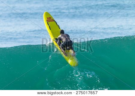 Lifeguard Black African Man Paddling Out To Ocean Backline Over Wave On Yellow Surf Rescue Craft.