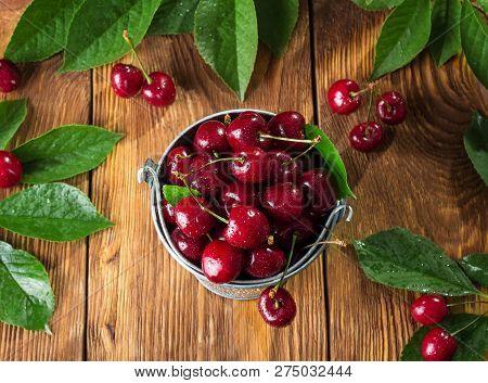 Top View. Fresh Juicy Berries Cherries In Bucket On Wooden Background