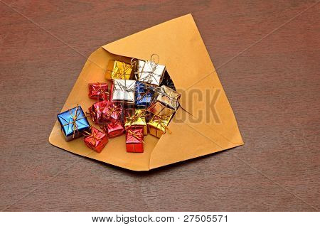 colorful gift boxes with envelope on wood background