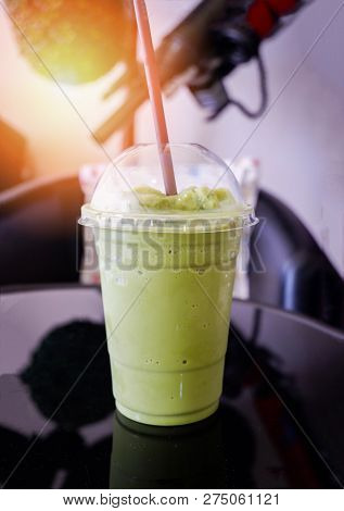 Milk froth green tea smoothie / Iced green tea in plastic cup smoothie matcha green tea latte frappe and straw on table in coffee shop poster