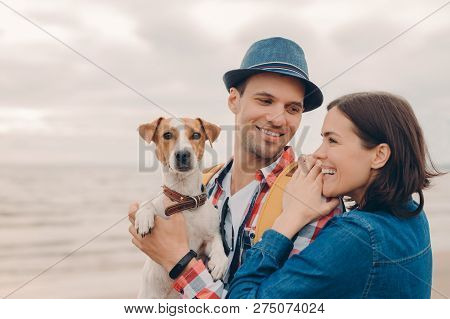People, Vacation Concept. Horizontal Shot Of Pleased Young Woman And Man Dressed In Hat And Shirt, C