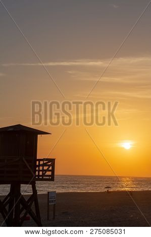 The Sun Setting Behind A Lifeguard Tower In Rota, Spain.