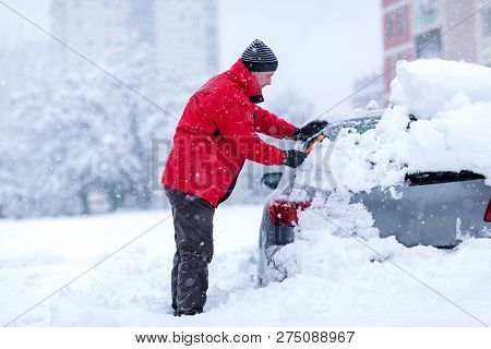 Young Man Cleaning Frozen Car Covered Snow At Winter Day,