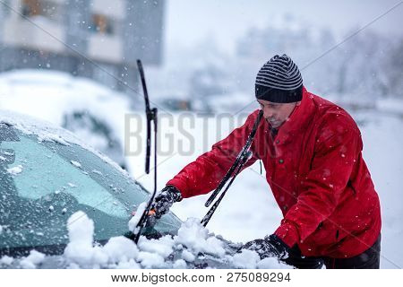 Brush In Man's Hand. Man Clears Snow From Icy Windshield Of Car..