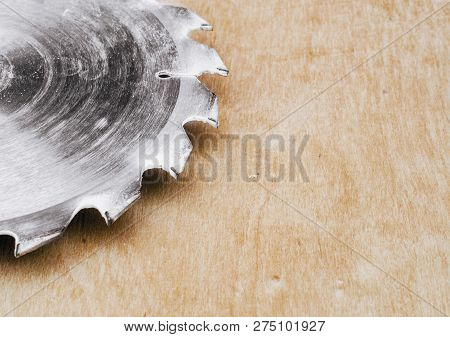 Circular metal saw on background polished plywood. Carpentry workshop, work tools poster