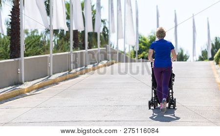 young healthy mother jogging while pushing a baby stroller at city park
