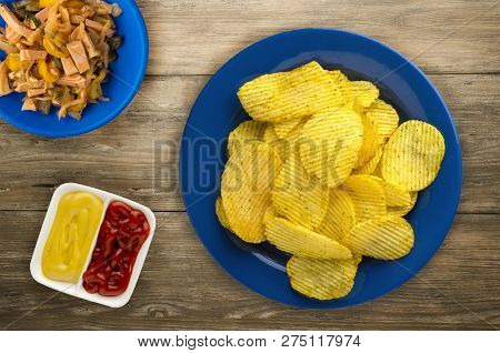 Potato Chips On A Plate. Chips On A Wooden Background .