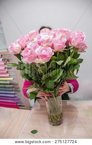 A Florist Puts In A Vase A Large Bouquet Of Large Pink Roses In A Florist Shop