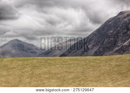 Empty Field With Three Hills In The Background Landscape
