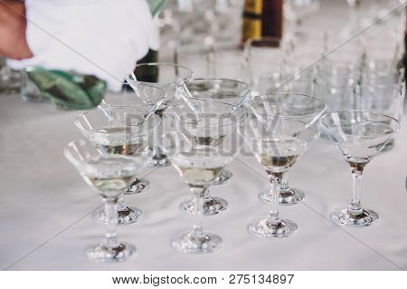 Waiter Pouring Martini In Crystal Glasses On Table Party At Wedding Reception. Martini Row Drinks At