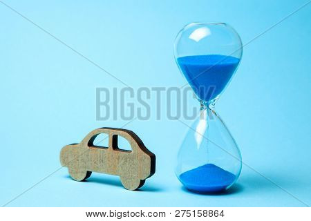 Depreciation Or Depreciation Of The Car Over Time. Wooden Car And Hourglass On Blue Background. Old