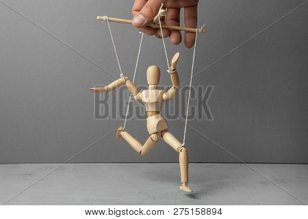 The Puppeteer Holds The Doll By The Rope. The Doll Does Not Obey The Puppeteer