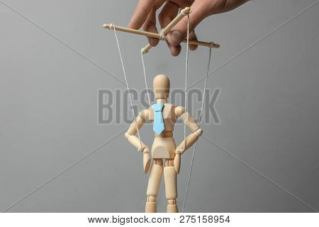 Businessman Leader In Tie On Gray Background. Deryannaya Doll On The Threads That Pulls The Puppetee