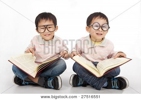 Happy kids with big book wearing black glasses