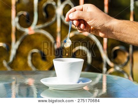 Hand Of Man Hold Coffee Spoon, Or Coffe Cup. Cappuccino And Black Espresso Coffe Cup. Coffee Drink.