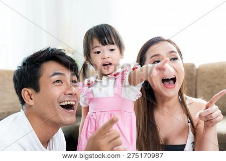 Happy Family Playing Toys With Daughter At Home.