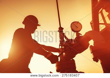 Oil Worker Is Checking The Oil Pump On The Sunset Background.