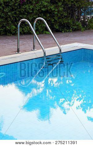 Metal Staircase With Railing In The Pool