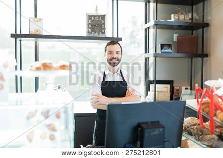 Portrait Of Owner Standing Arms Crossed At Counter In Bakery Shop