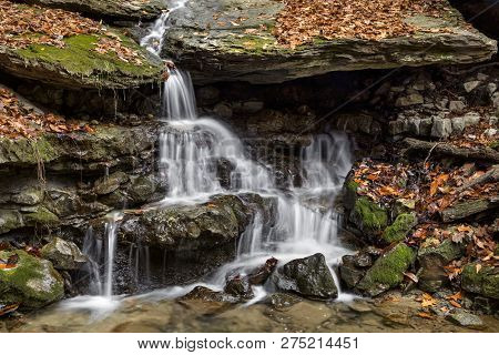 A Small Waterfall Cascades Down Mossy Rocks With Autumn Leaves All Around.