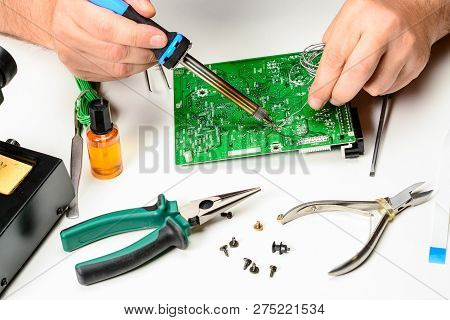 The Electronics Technician Replaces The Non-working Element Of The Electronic Device With A Solderin