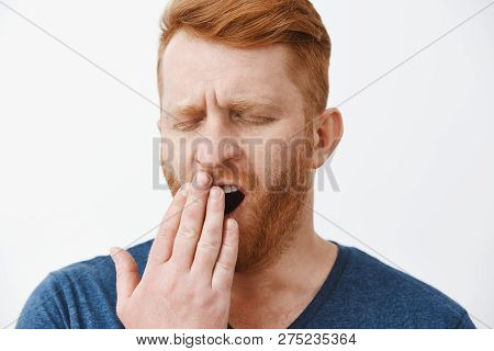 Headshot Of Tired Attractive Male Entrepreneur With Red Hair And Beard, Yawning With Closed Eyes, Co