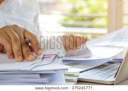 Teacher Holding Pen By Hand For Checking Student Homework Assignments On Desk In School Office. Unfi