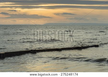 Wooden Beach Groin Semi Submerged By Tide At Sunset. British Col
