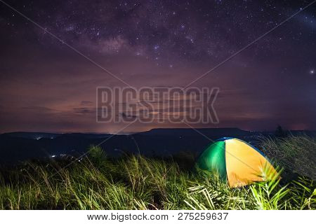 Tent areas on hill night sky star Milk Way galaxy / colorful hiking camping tent on grass green field on the mountain - landscape area camping tents in the wild with cloud galaxy milk way sky