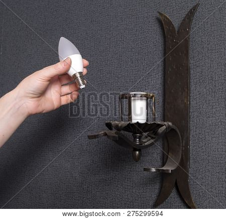 A woman's hand inserts an led light bulb into the wall lamp. poster