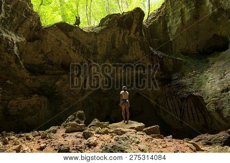 Traveler girl ln tropical cave nature in vacation. Young girl traveler looking to ancient cave drawing in nature. Traveler in cave in nature. Girl traveler in ancient cave nature in tropical forest. Traveler. Vacations. Tropics. Girl. Cave. Nature