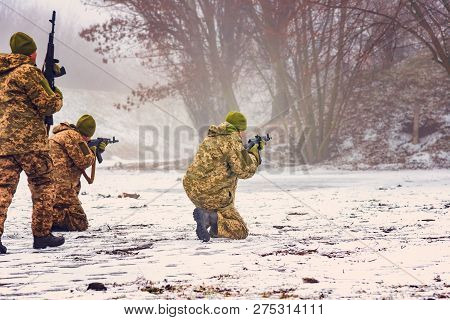 Three Militant Soldiers Conduct Aimed Fire In A Training Camp In The Winter With Automatic Weapons.