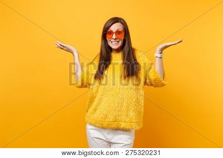 Portrait Of Pretty Guilty Young Girl In Fur Sweater White Pants Heart Orange Glasses Spreading Hands