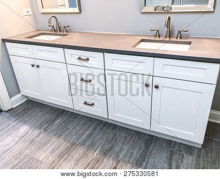 Spacious bathroom. White cabinets with counter in bathroom. White sinks in bathroom space, bathroom sinks, bathroom faucets, bathroom mirrors, floor, tiles. Wooden cabinets bathroom concept