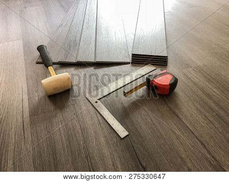 Luxury flooring concept. Vinyl plank laminate floor. Worker preparing for new floor installation. Tools on the floor. Hardwood floor. Tile floor. Vinyl floor. Modern flooring tiles.