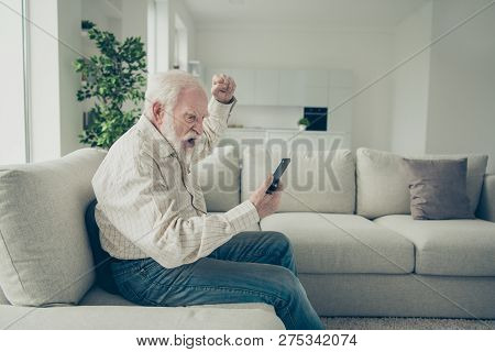 Profile Side View Portrait Of Mad Stylish Old Man Wearing Checked Shirt Sitting On Divan Holding In
